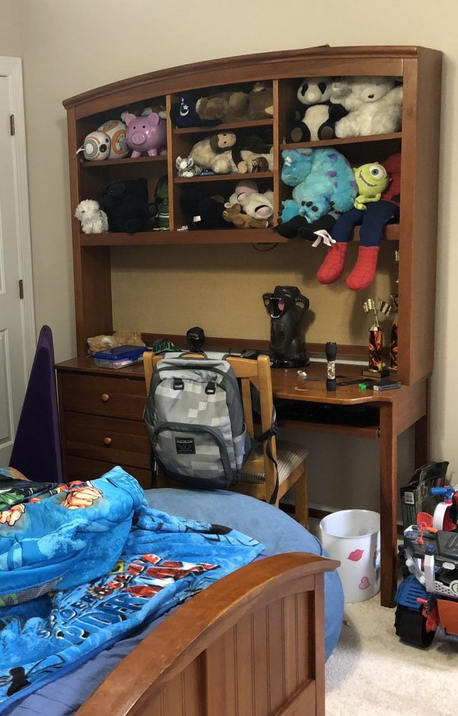 desk in boys bedroom with lots of stuffed animals and items stored on it.