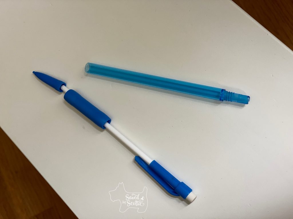 dismantled mechanical pencil on white drawer front