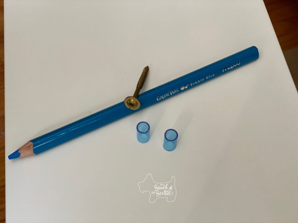 blue colored pencil with blue plastic spacers and a cabinet screw on a white background