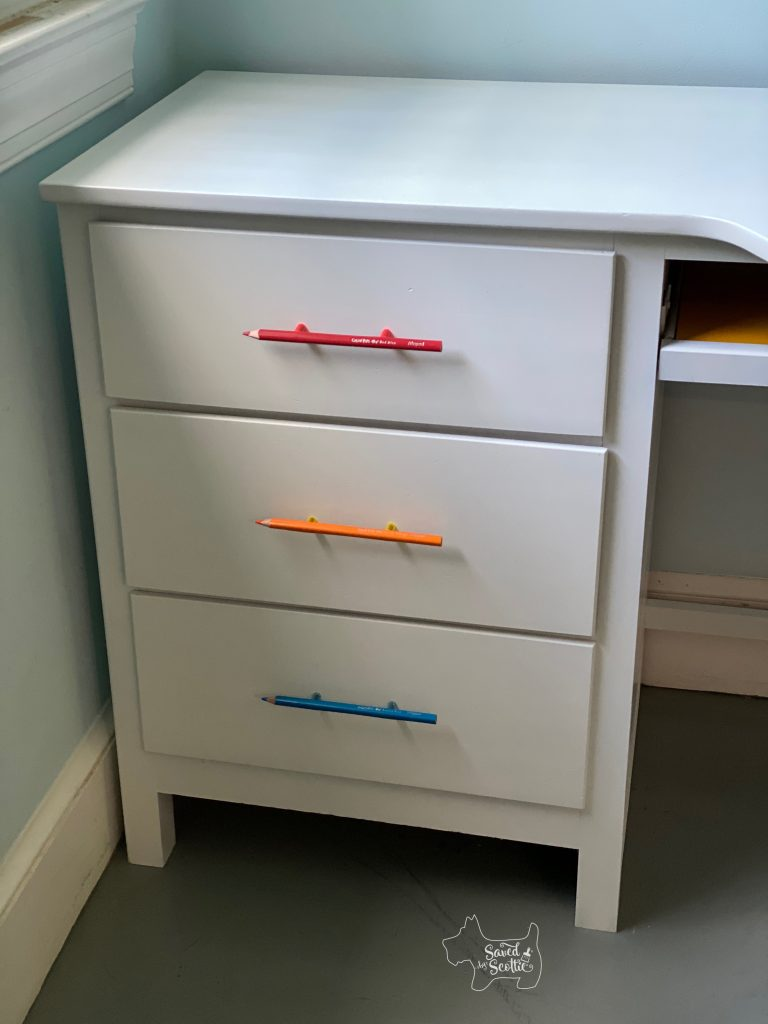 close up of drawer portion of desk showing colored pencil unique drawer pulls