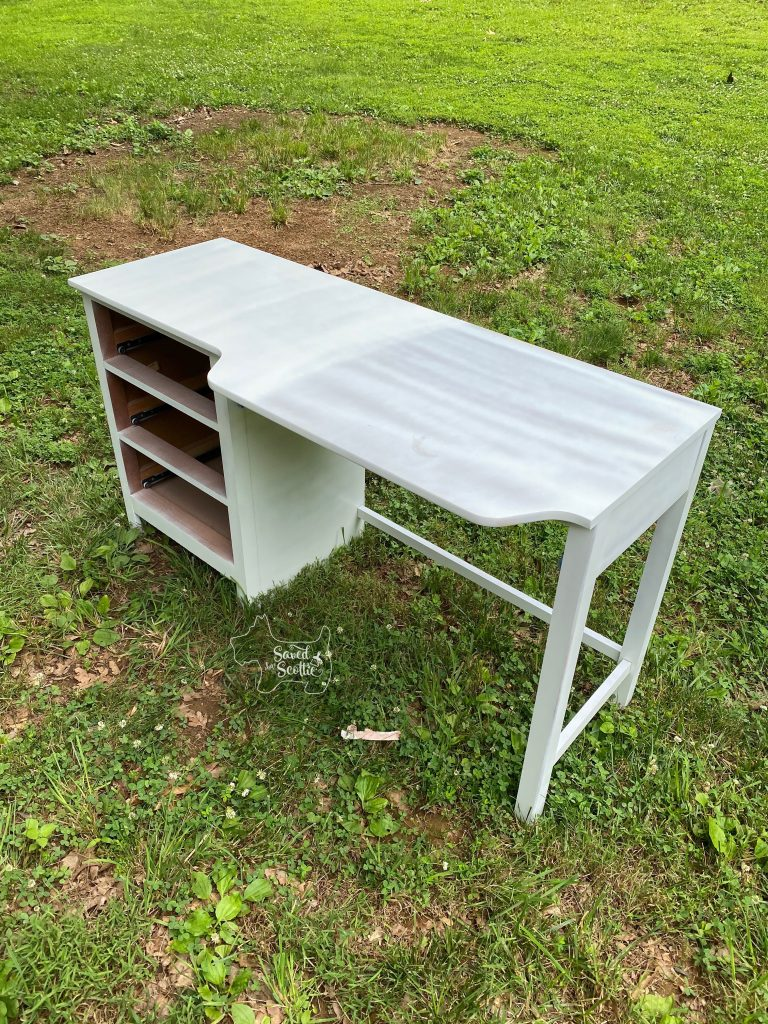 wood desk outside with primer and partial white paint coat applied