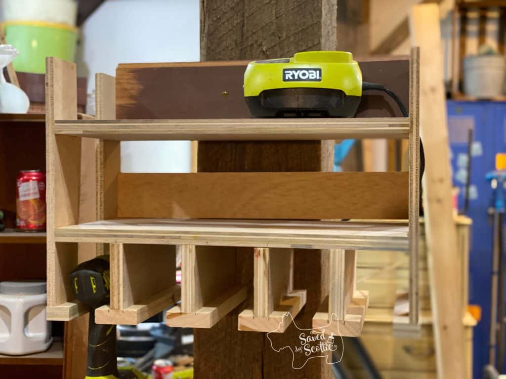 tool charging station made from scrap wood hanging on post in workshop setting.