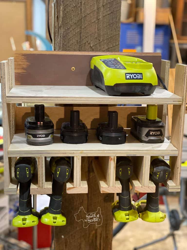front view of tool charging station made from scrap wood with ryobi charger, battery and drills inserted. Hanging on thick post in workshop setting.